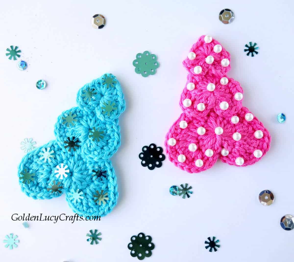 Two crocheted Christmas trees in pink and turquoise colors.