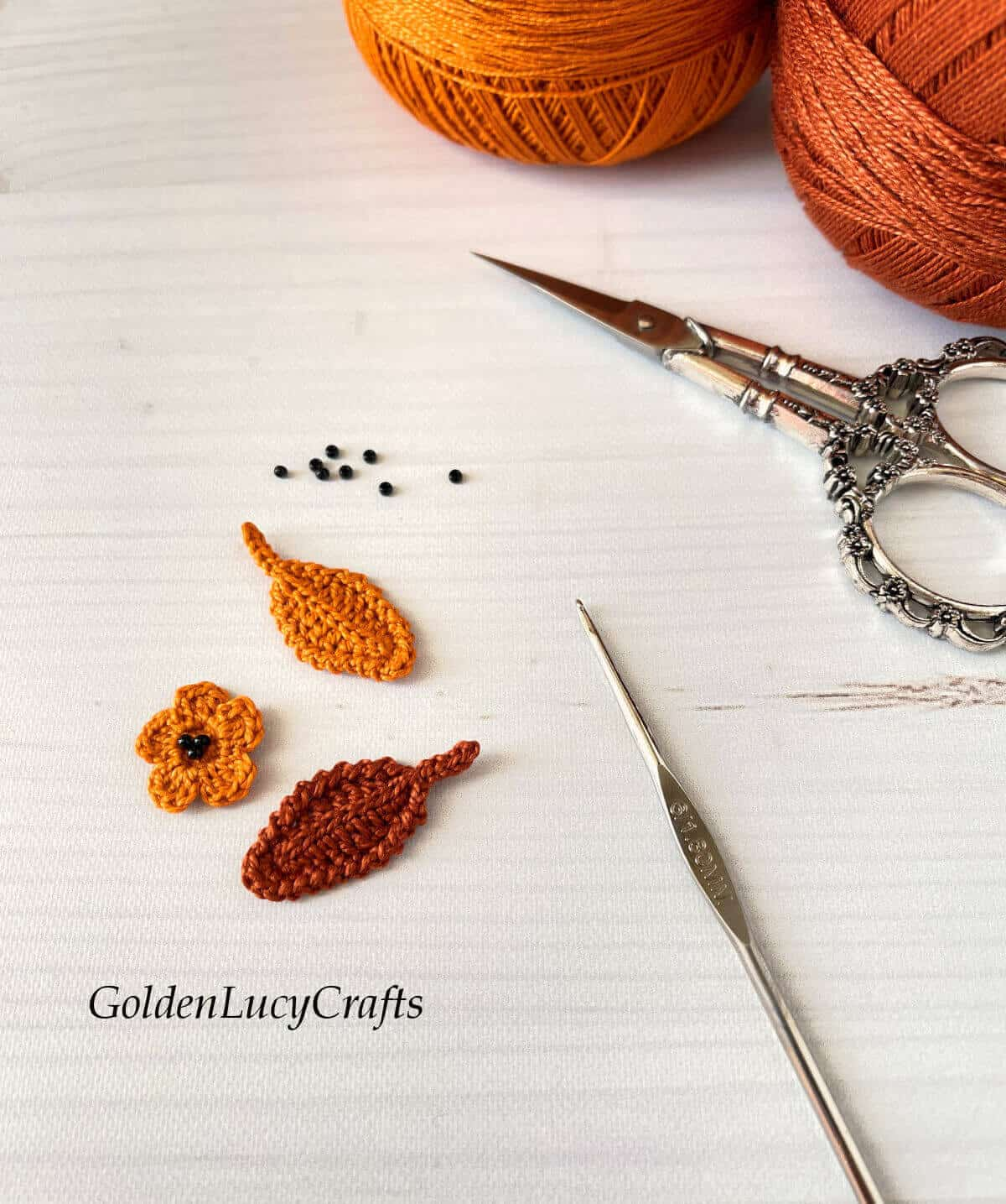 Crocheted flower, two leaves, tiny beads, crochet hook, scissors and two balls of threads.