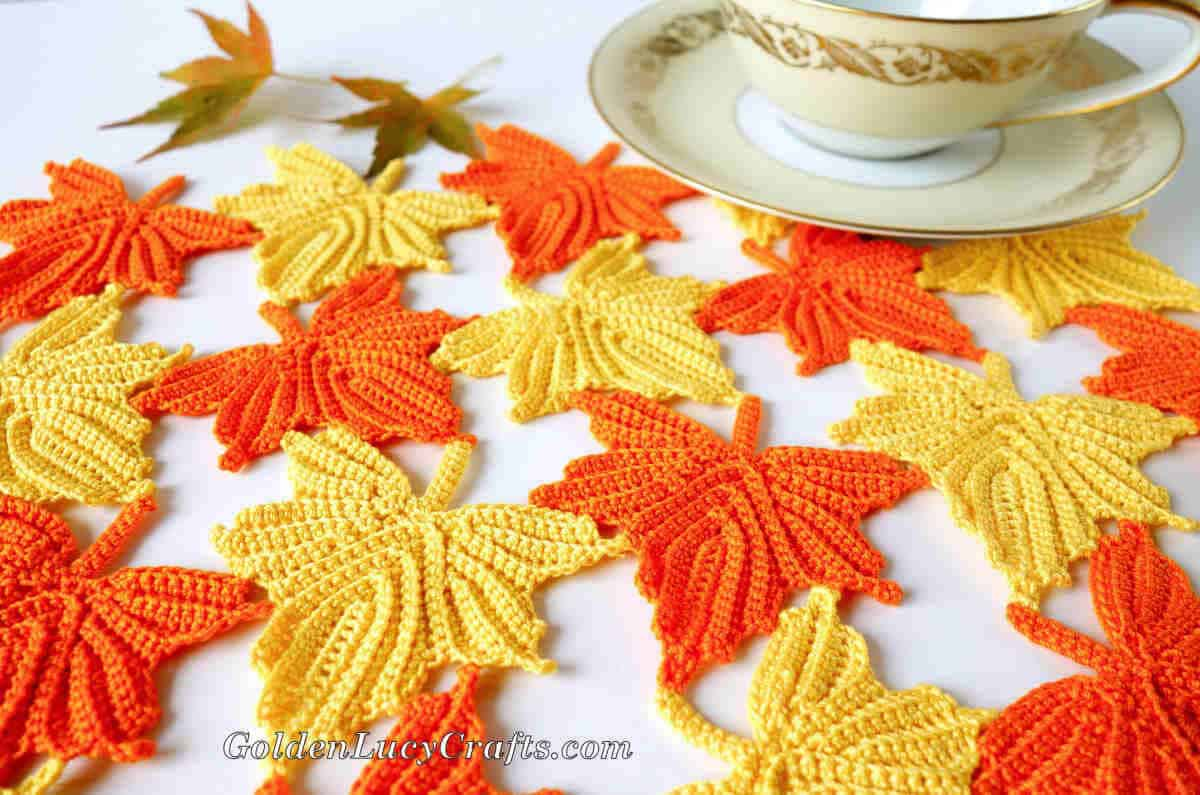 Crocheted maple leaves table decor, tea cup in the background.