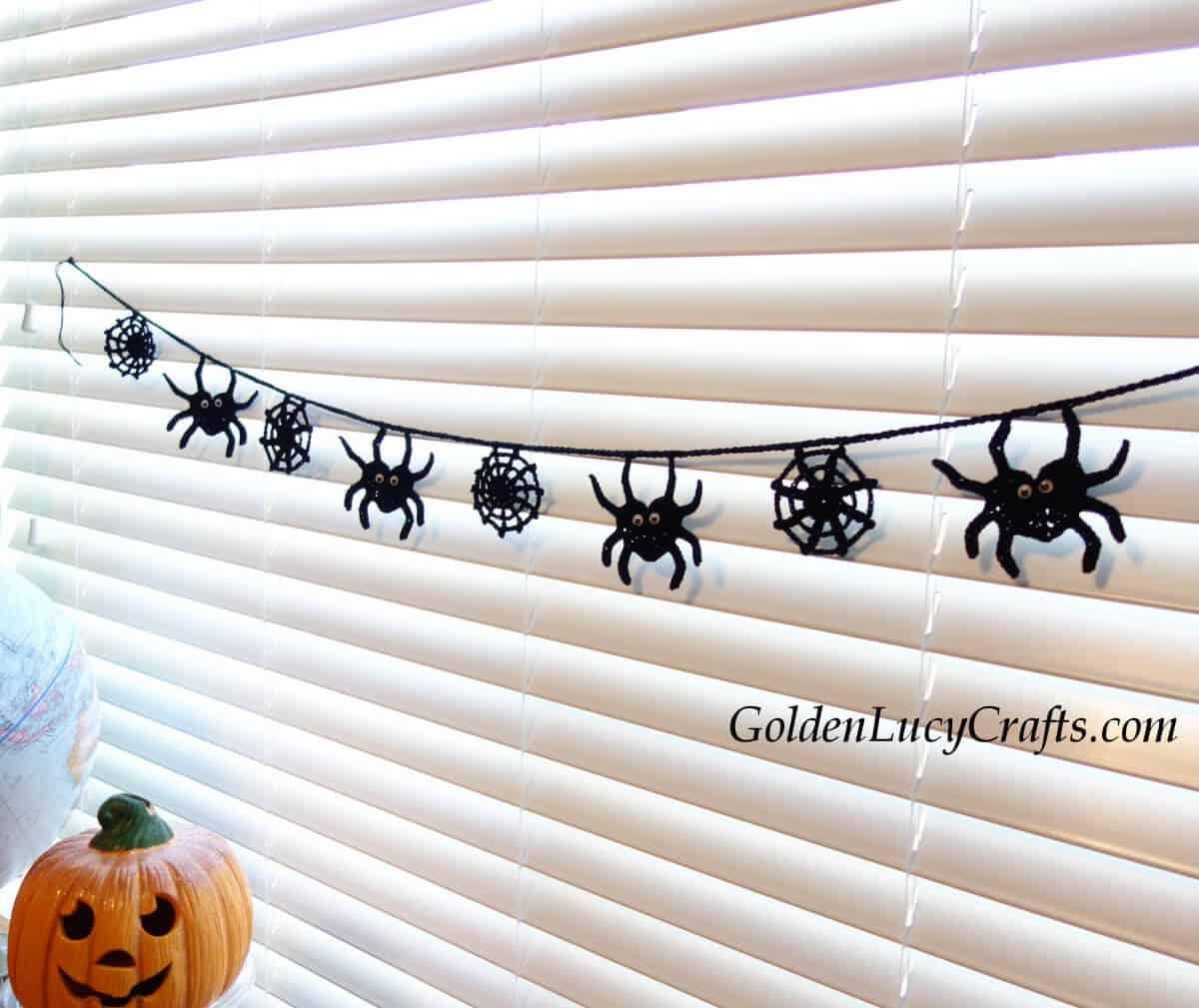 Crocheted Halloween garland hanging on the window.