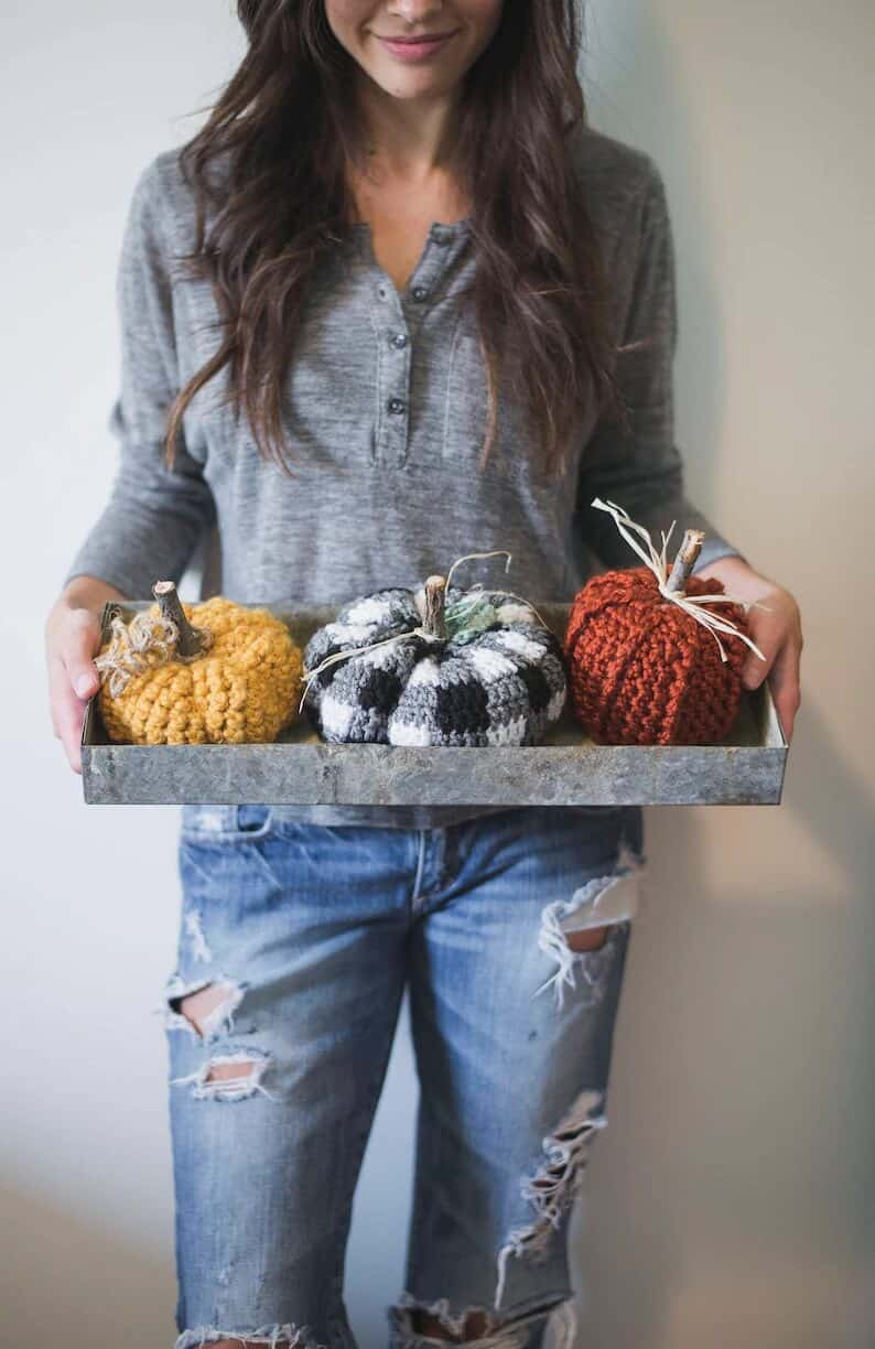 Model is holding three crocheted pumpkins on a tray.