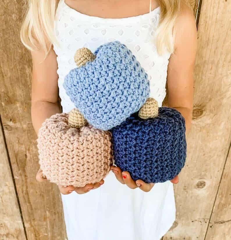 Model is holding crochet pumpkins.