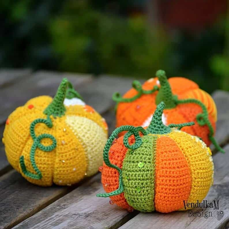 Three crocheted pumpkins on the wooden surface.
