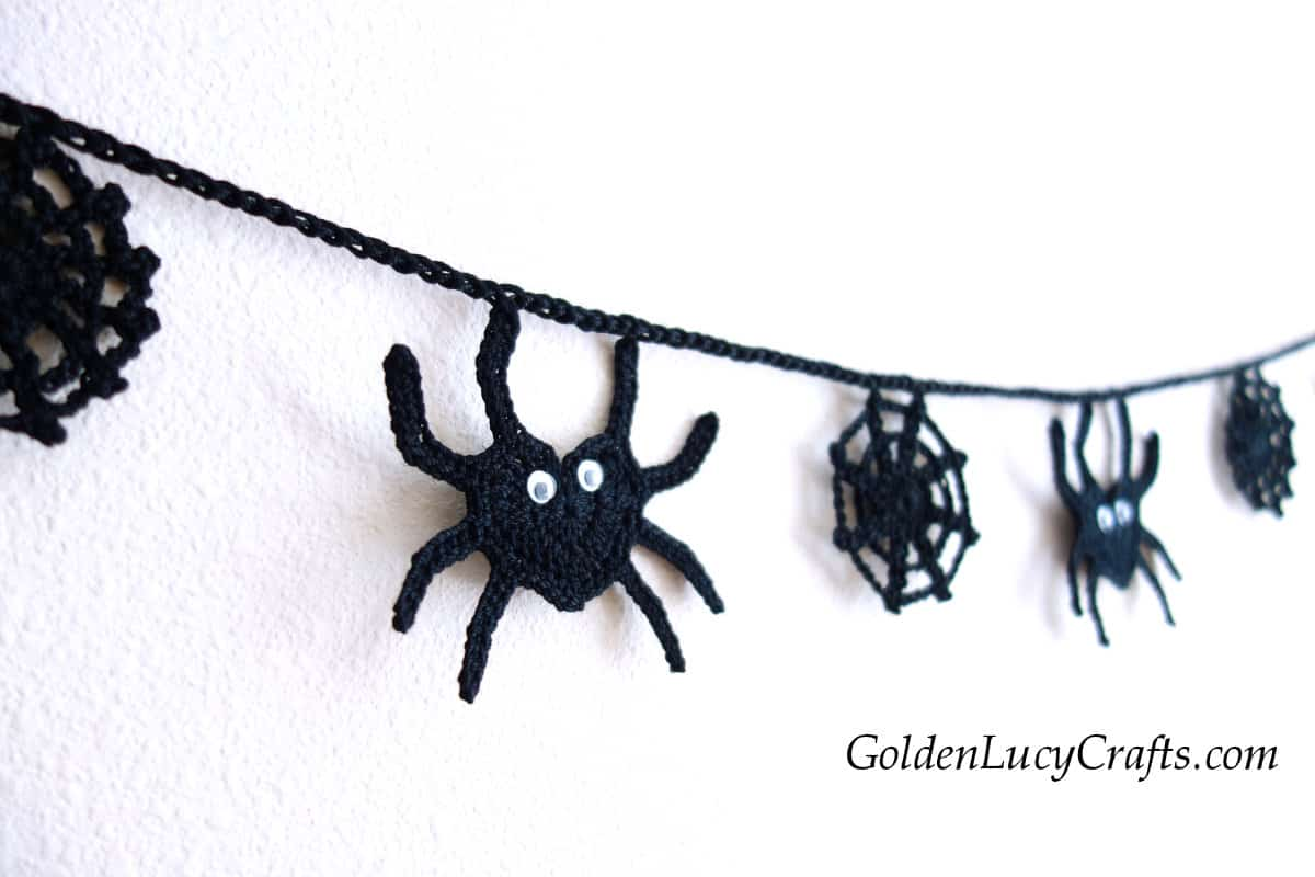 Spiders and spider web crochet garland on the wall.