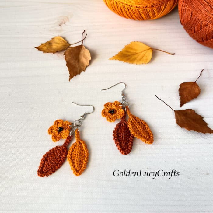 Crochet fall earrings, leaves and two balls of thread in the background.