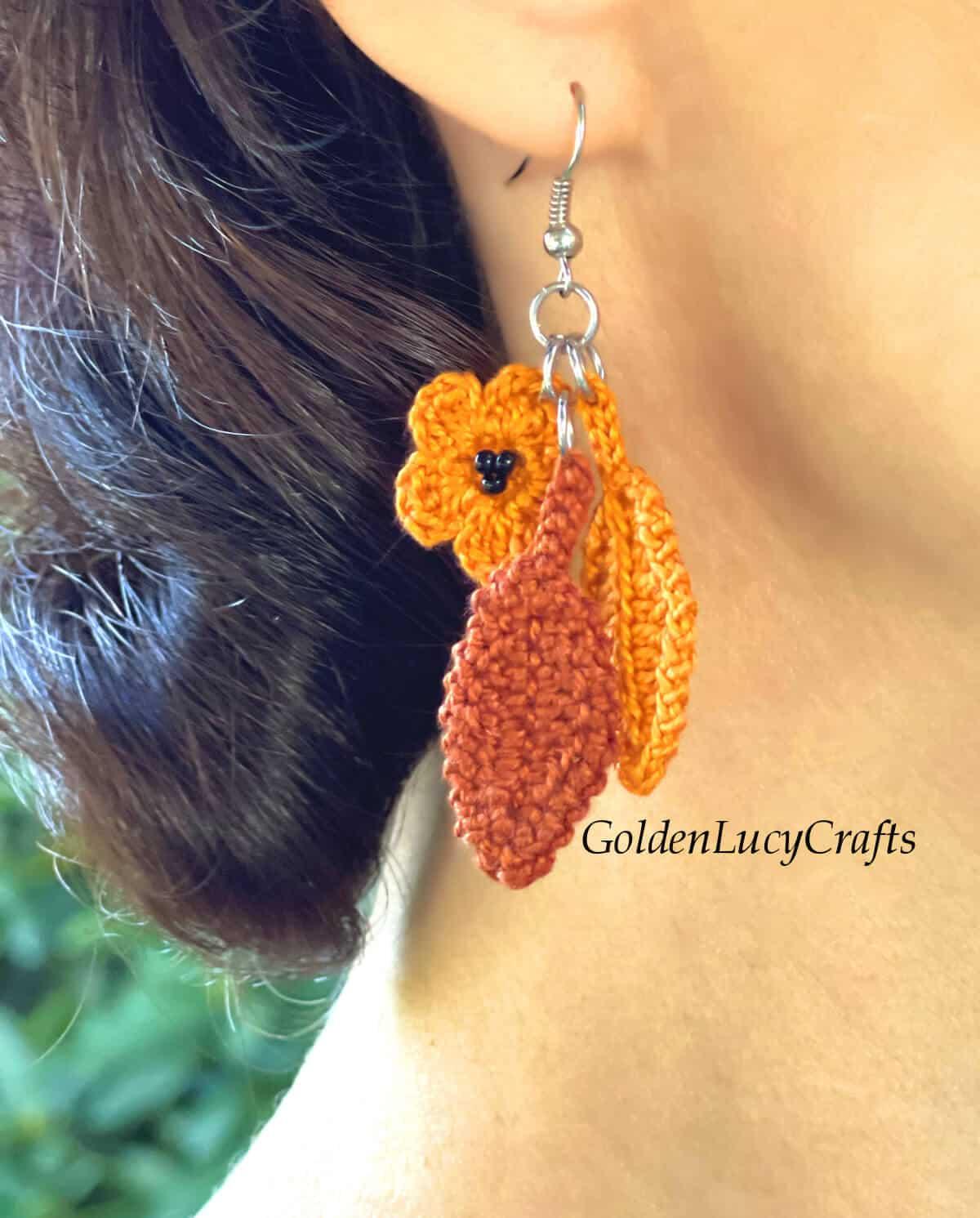 Model is wearing crocheted Fall earrings.