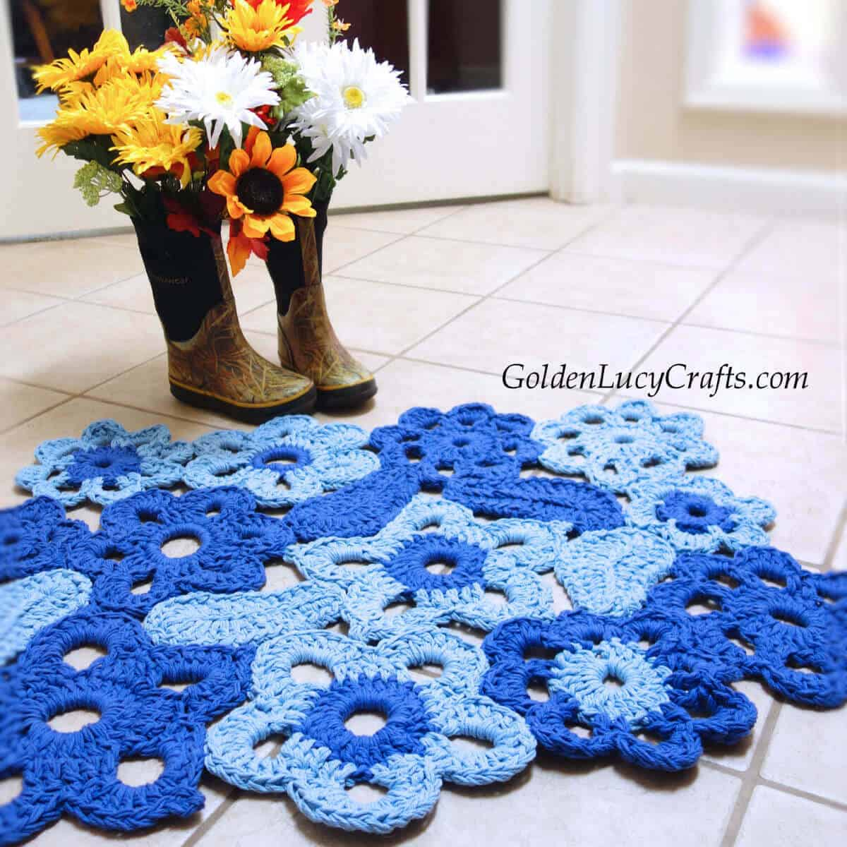 Crocheted flower rug on the floor, rainboots with flowers next to the rug.
