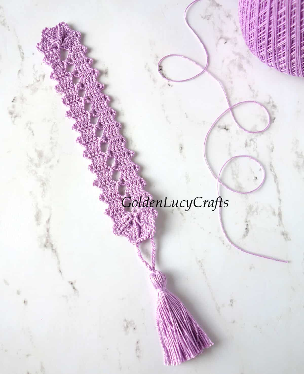 Crochet bookmark and ball of thread next to it.