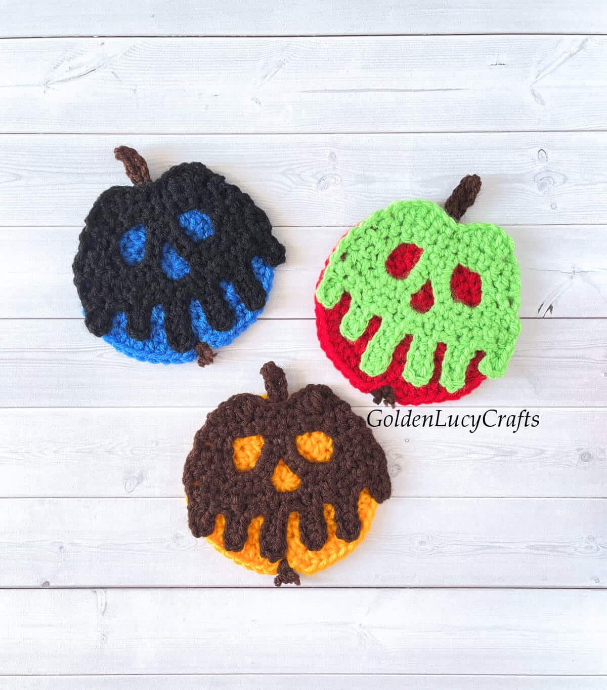 Three crocheted poisoned apples in different colors.