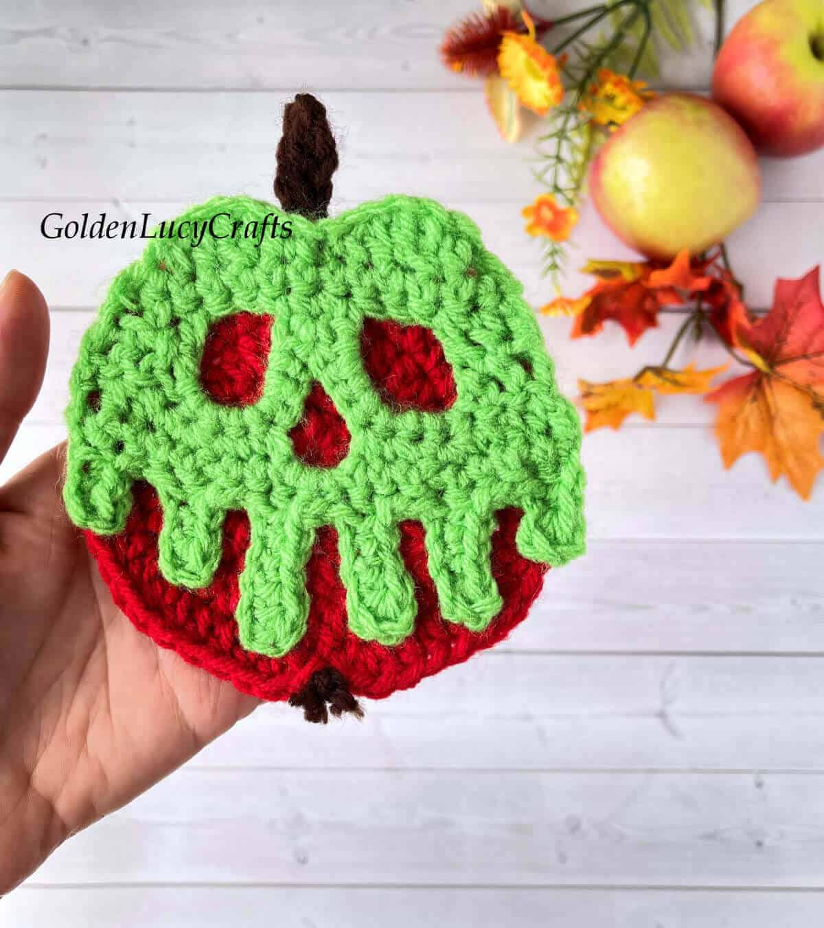 Crocheted poisoned apple ornament in the palm of a hand.