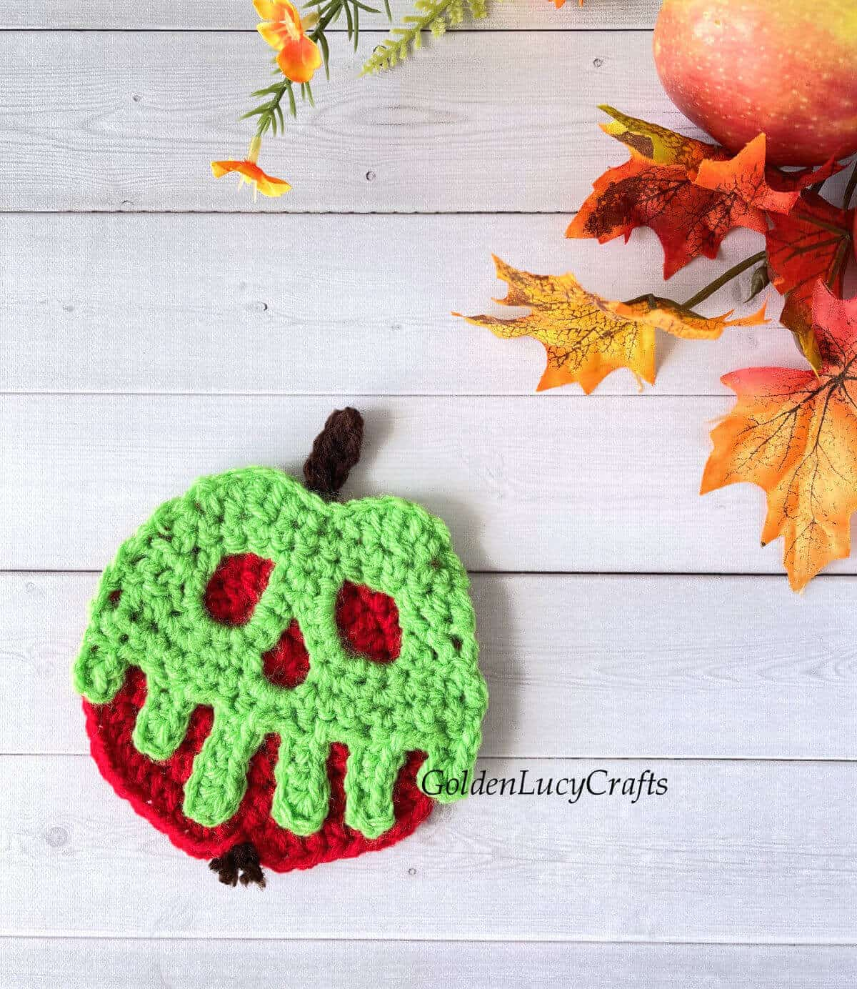 Crocheted poisoned apple applique laying on some surface.