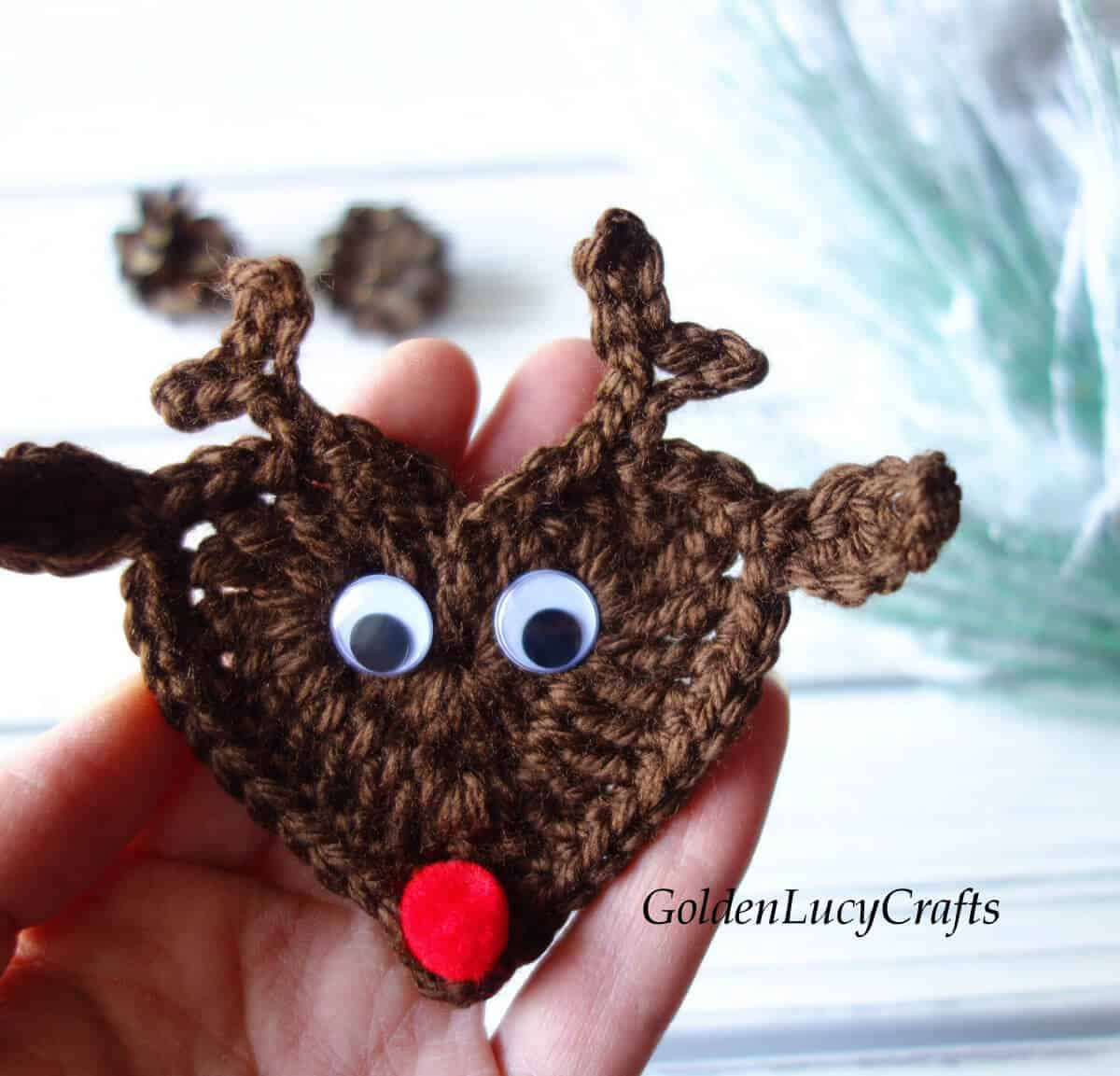Crocheted reindeer applique in the palm of a hand.