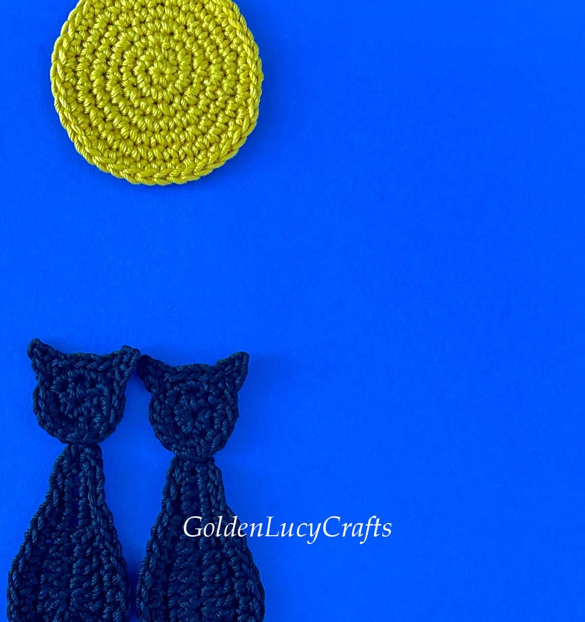 Crocheted black cats and moon on dark blue background, close up picture.