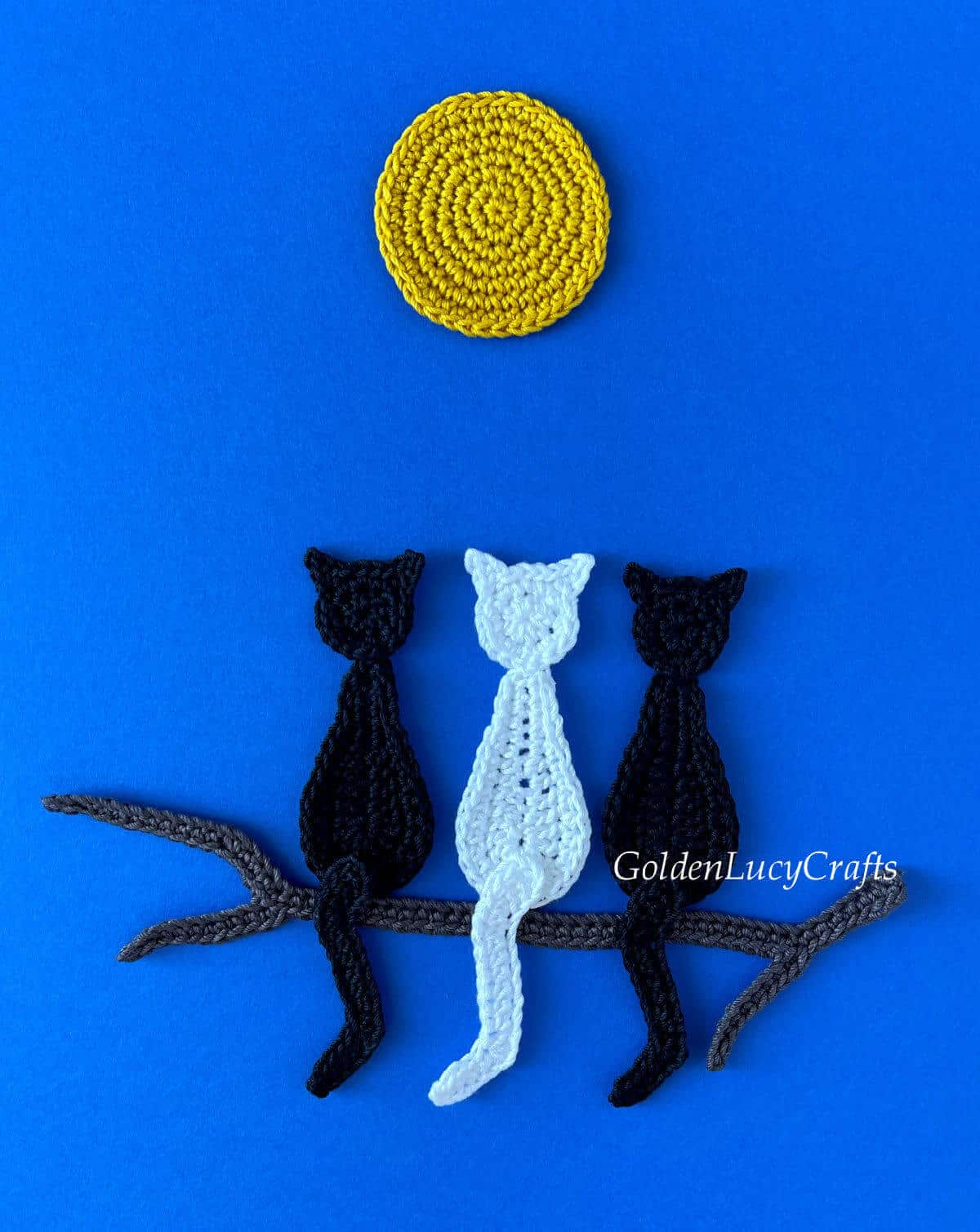 Crocheted two black and one white cats sitting on a tree branch under a full moon on dark blue background.