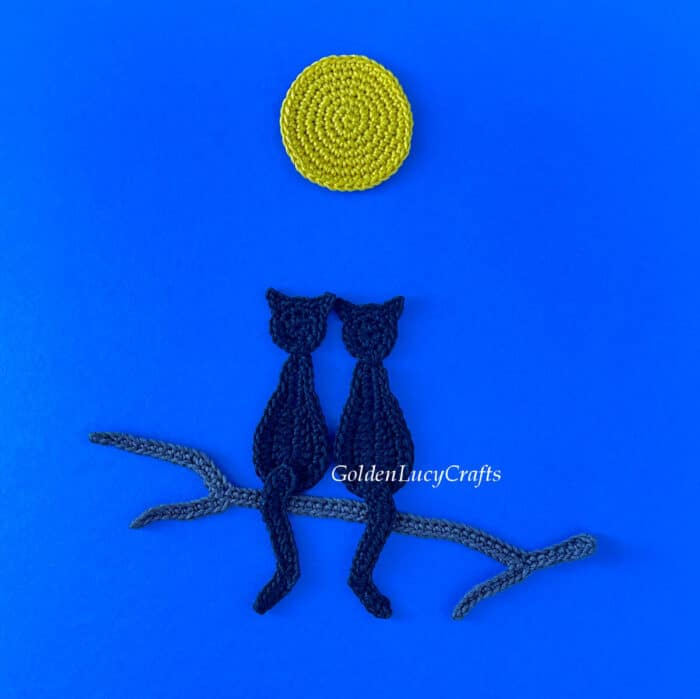 Crocheted two black cats sitting on a tree branch under a full moon on dark blue background.