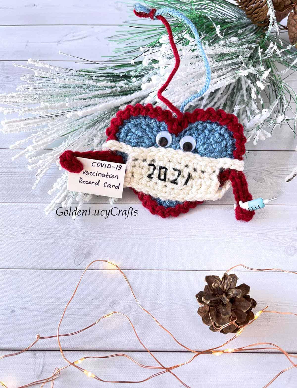 Enfeite de Natal 2021 em crochê de coração usando uma máscara.