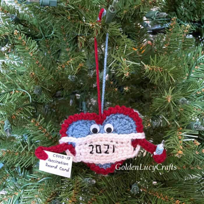 Christmas ornament crocheted heart in mask hanging on Christmas tree.