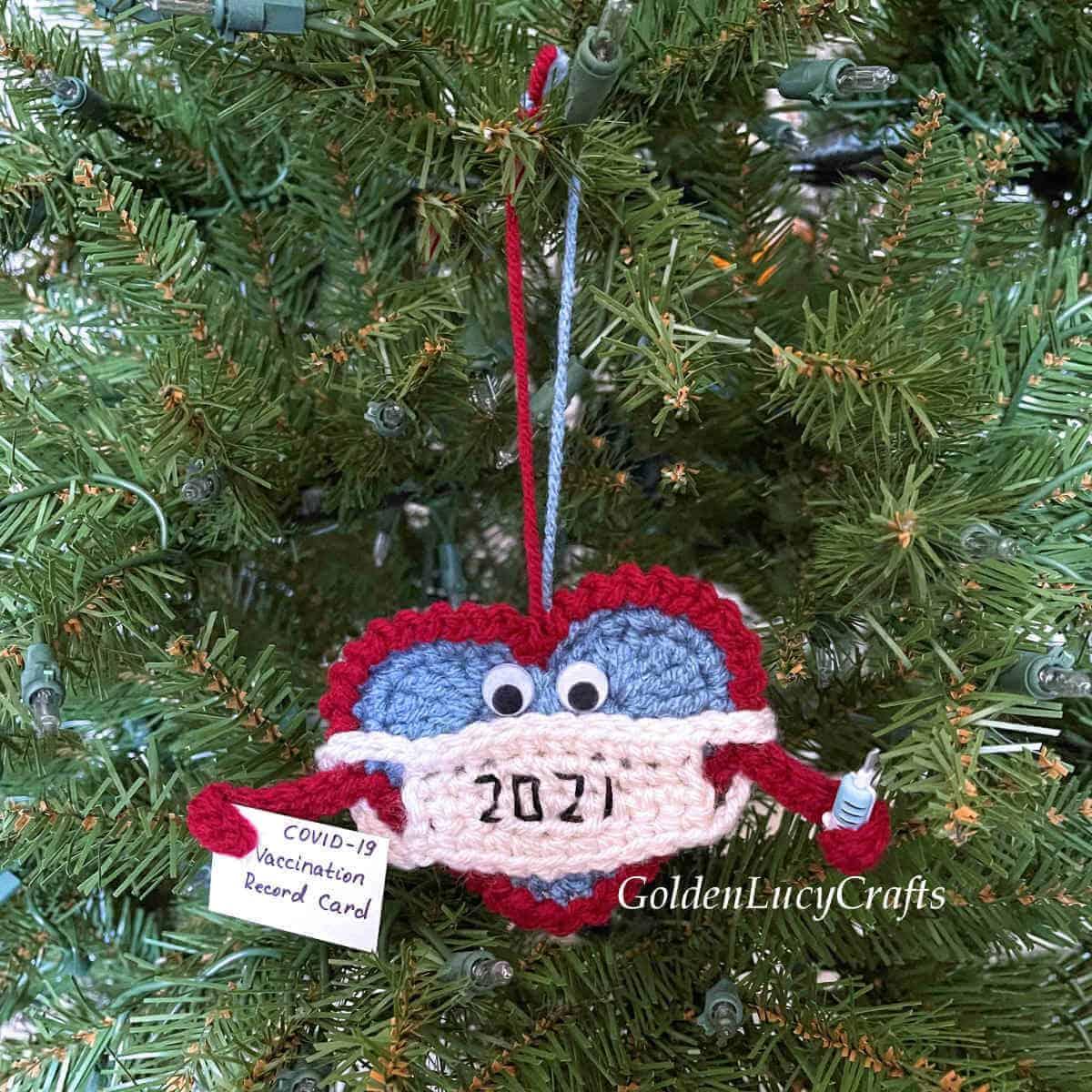 Enfeite de Natal de crochê de coração em máscara pendurada na árvore de Natal.