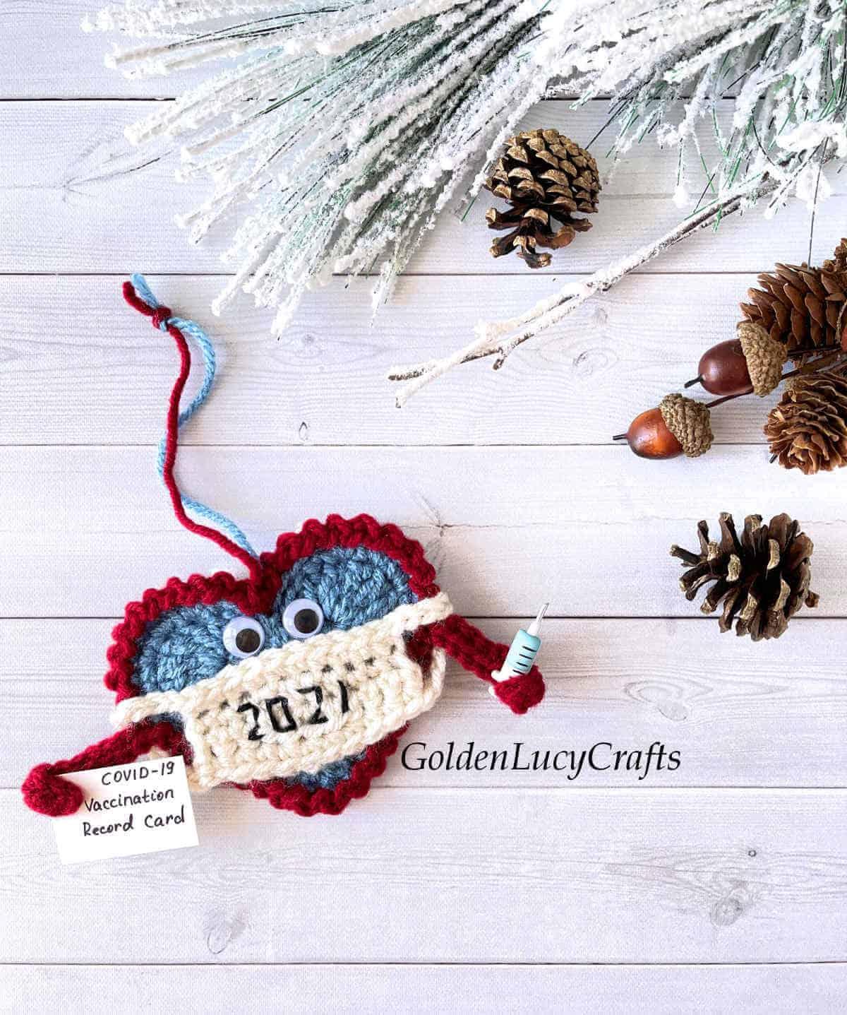 Enfeites de Natal 2021 de crochê, pinhas, bolotas e galho de árvore de Natal ao fundo.
