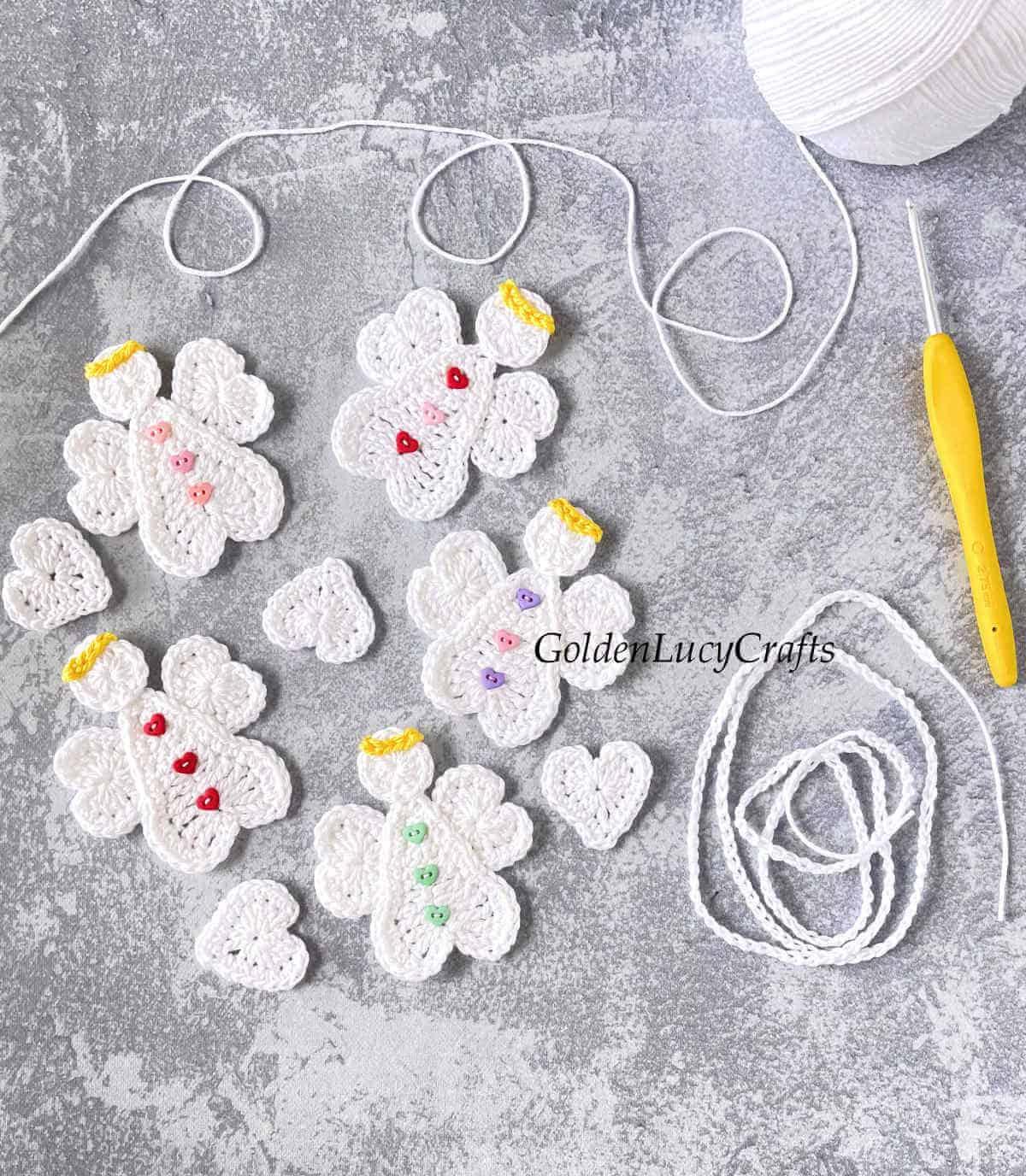 Anjos de crochê, corações, fio branco e agulha de crochê.