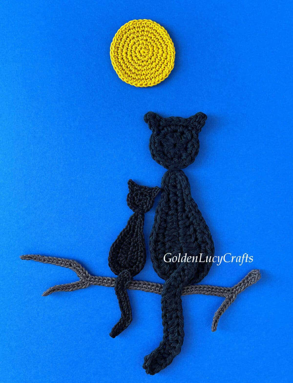 Crocheted one big and one small black cats sitting on a tree branch under a full moon on dark blue background.