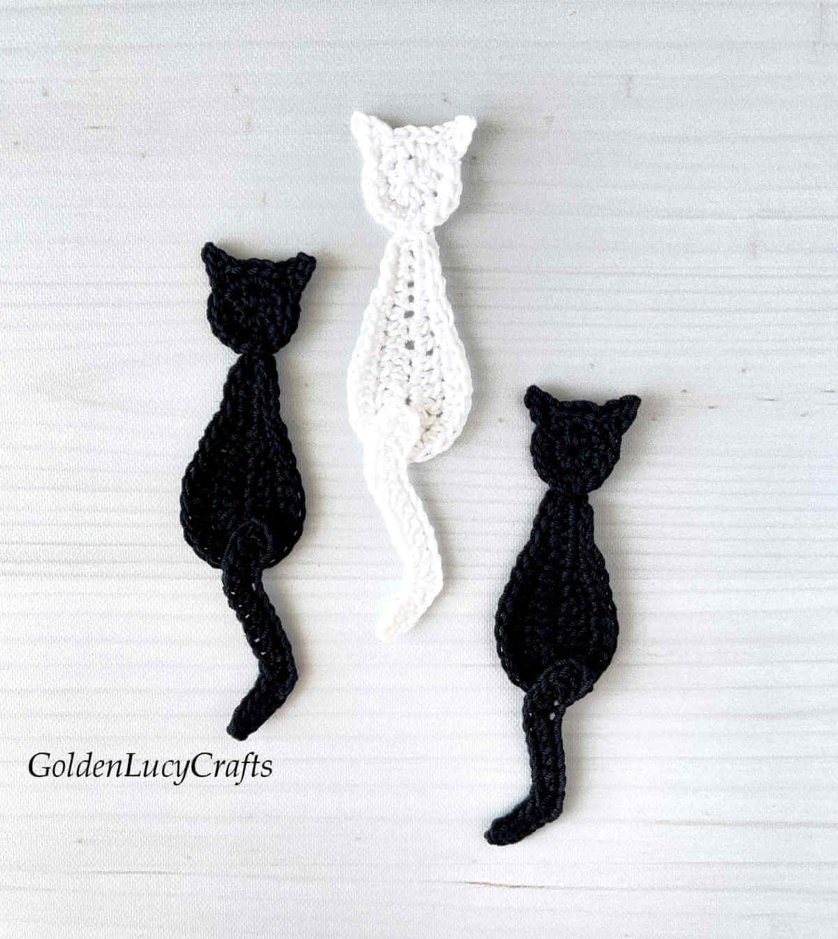 Two black cats and one white cat crochet appliques.