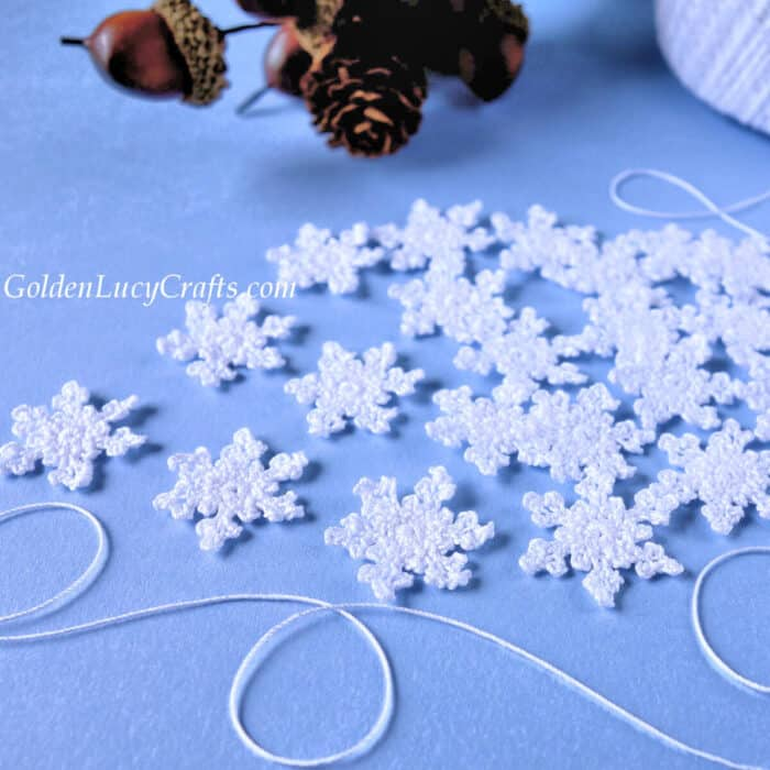 Crocheted small white snowflakes, white thread, pine cone in the background.